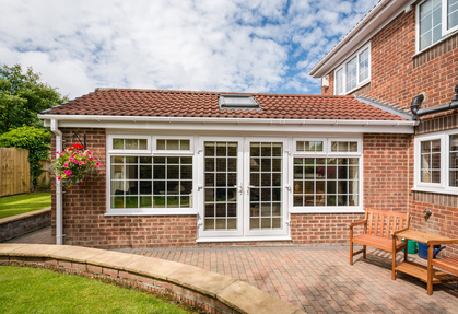 Modern Sun room / conservatory extending into the garden, surrounded by a block paved patio